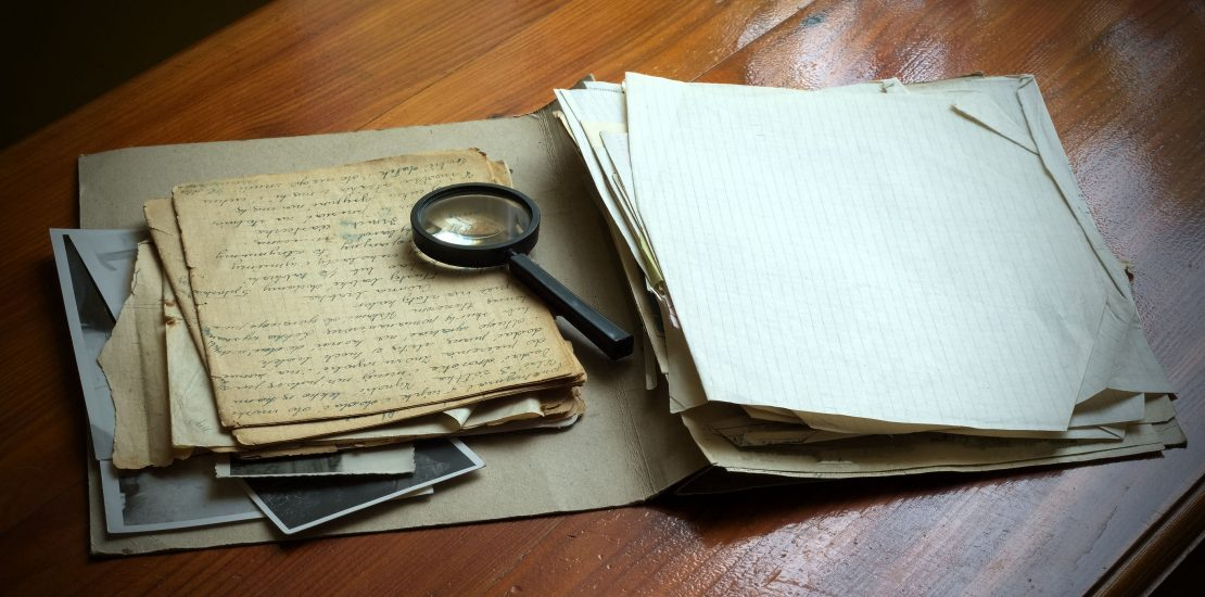 30960431 - vintage documents with magnifying glass investigation concept